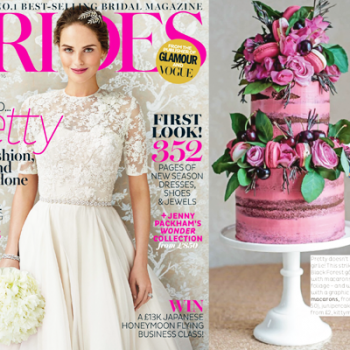 Bright pink semi-naked cake with cherries, macarons and roses in Brides magazine